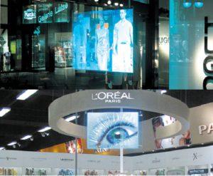 Ejemplos de una de las tecnologías multimedia analizadas para el proyecto (pantallas holográficas). Estas pantallas son proyecciones holográficas que muestran imágenes proyectadas hacia atrás de 30 a 35º. El resto de la luz no se considera, lo que genera imágenes muy brillantes y contrastadas, incluso en entornos muy iluminados. Estas pantallas permiten a los espectadores ver a través de ellas, y dan la sensación de estar suspendidas en el aire y de tener una profundidad 3D. Fuentes: Hugo Boss y L'Oréal Paris