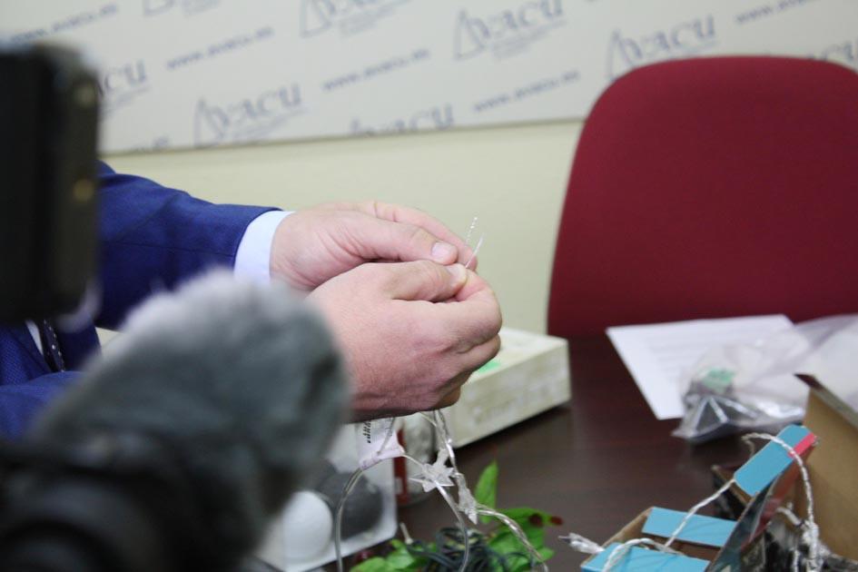 Juan José González Tarrago, responsable de Laboratorio Lámparas y Luminarias de AIDIMME, mostrando ante los medios de comunicación la fragilidad del cableado de ciertas guirnaldas.