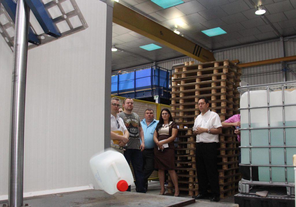 La delegación ucraniana en el Laboratorio de Mercancías Peligrosas observando un ensayo de caída que evalúa la resistencia de un envase o embalaje.
