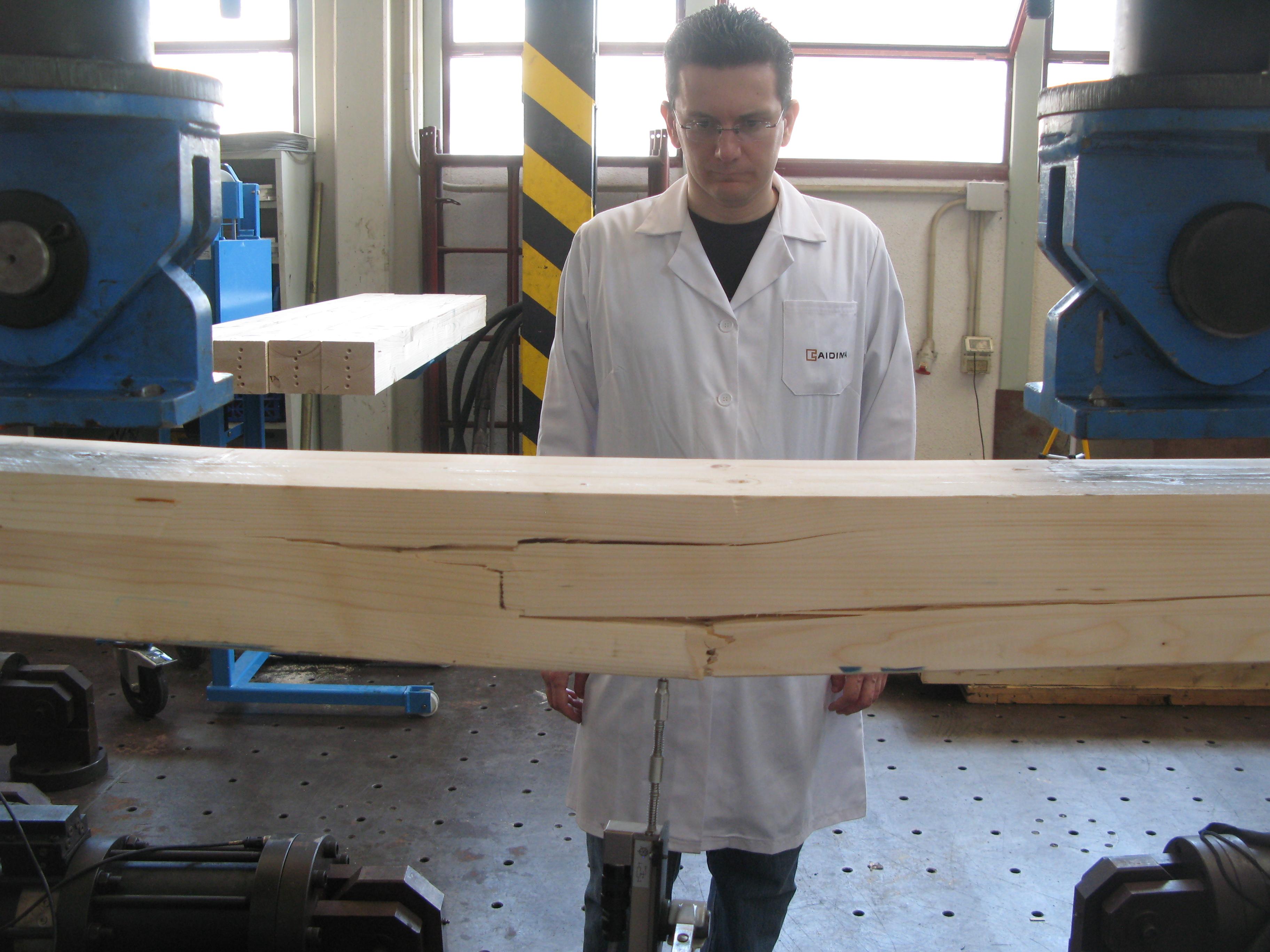Fotografía 3. Rotura de una viga de madera en un ensayo a flexión según la norma UNE-EN 408, mediante máquina universal de ensayos. Muy rara vez pueden realizarse estos ensayos destructivos en madera antigua y patrimonial; y para madera nueva tienen un coste muy elevado y se desaprovecha material.